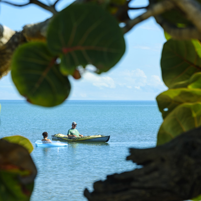 """""""Man in a kayak chats to a woman on a lilo on the sea"""" stock image"""