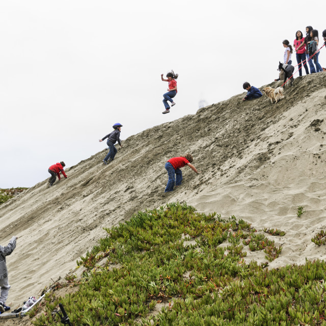 """Children playing on a sand dune"" stock image"