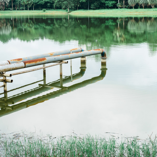 """""""The old rusty pump pipe in the lake"""" stock image"""