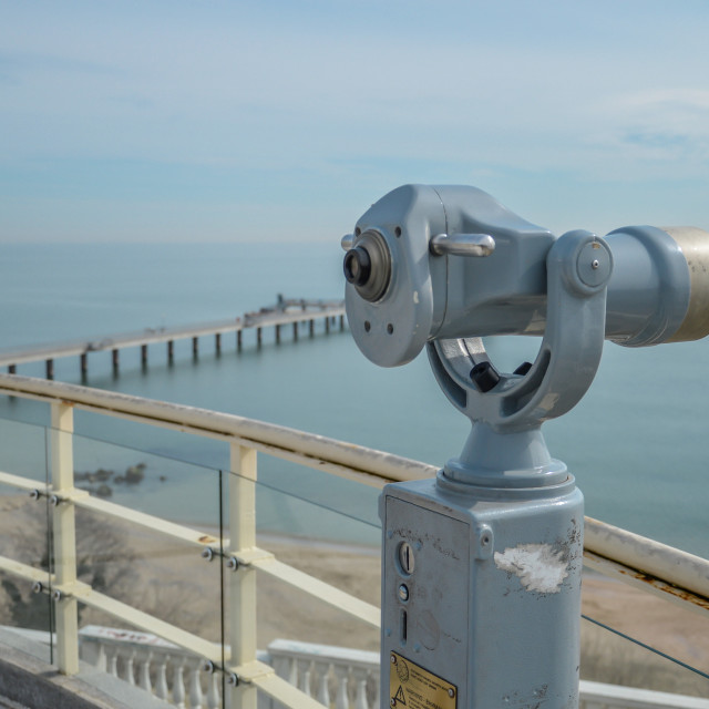 """A telescope with a bridge and blue sea and sky in the background"" stock image"