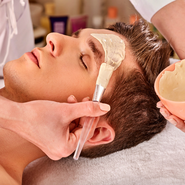 """Mud facial healing mask of man in spa salon."" stock image"