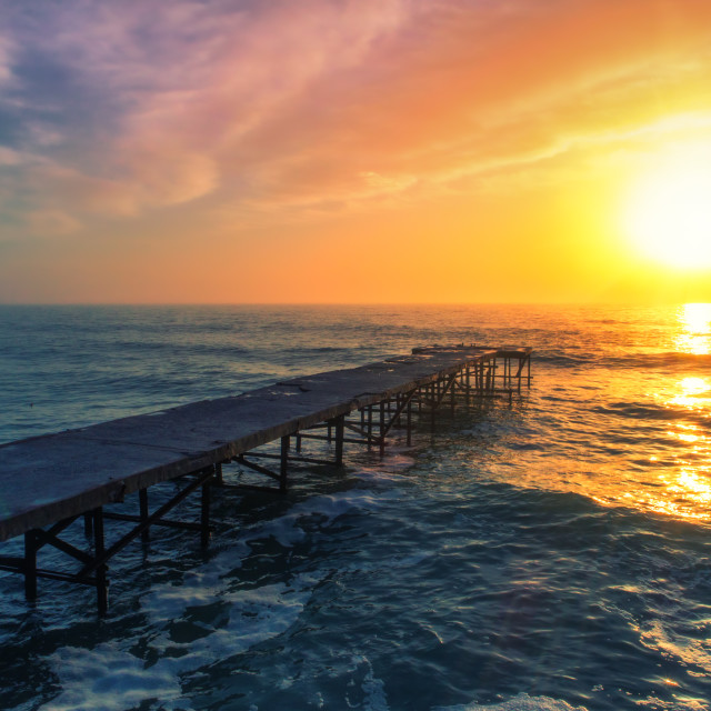 """""""Aerial view over the old broken bridge in the sea, sunrise shot."""" stock image"""