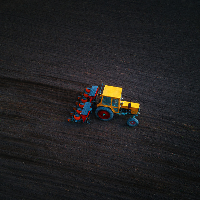 """Aerial view of tractor working on the harvest field"" stock image"