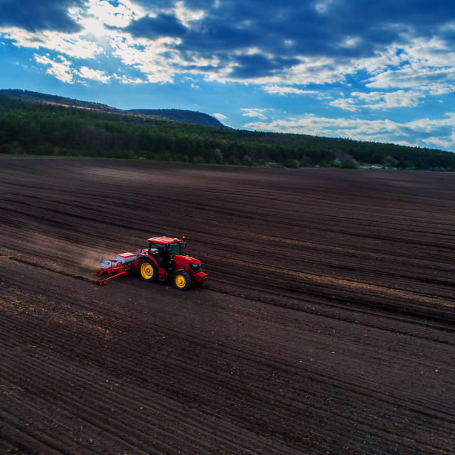 """""""Aerial view of red tractor preparing field"""" stock image"""