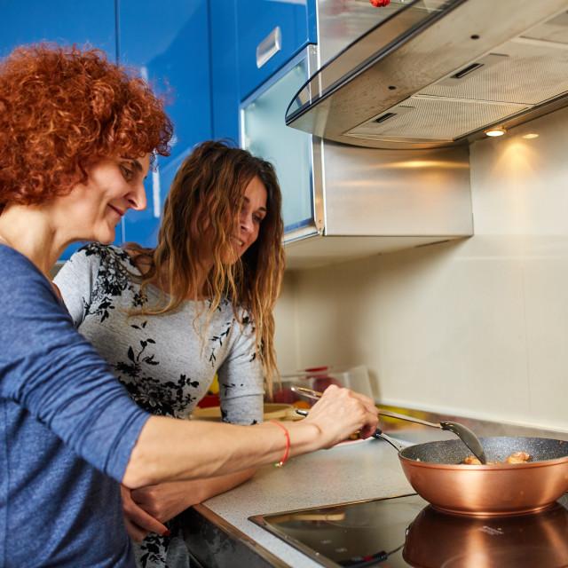 """Girlfriends having fun in the kitchen"" stock image"
