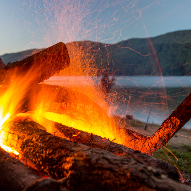 """Slow burning fire at lake shore"" stock image"