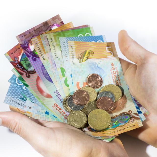 """Holding a bunch of New Zealand Dollars and coins"" stock image"