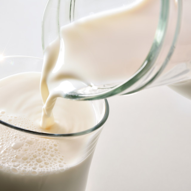 """""""Filling glass of milk with jug on white background"""" stock image"""