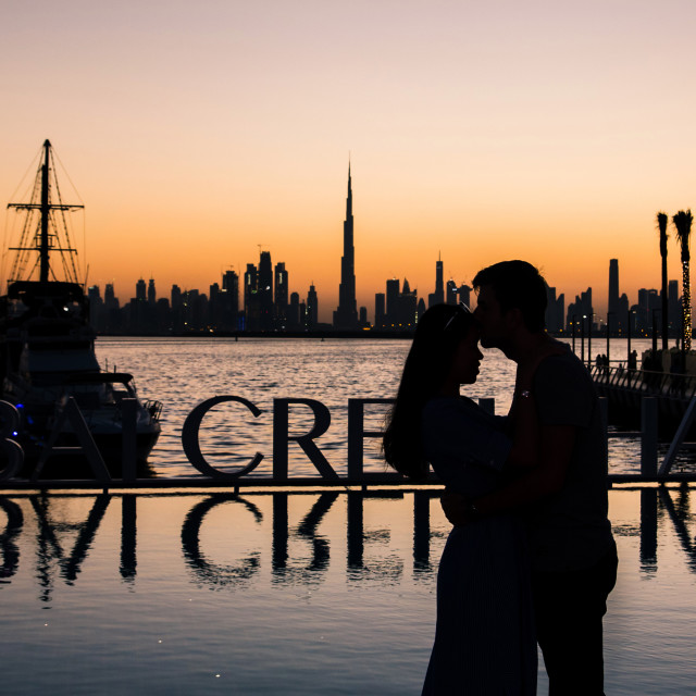 """Romantic couple hugging at sunset in Dubai"" stock image"