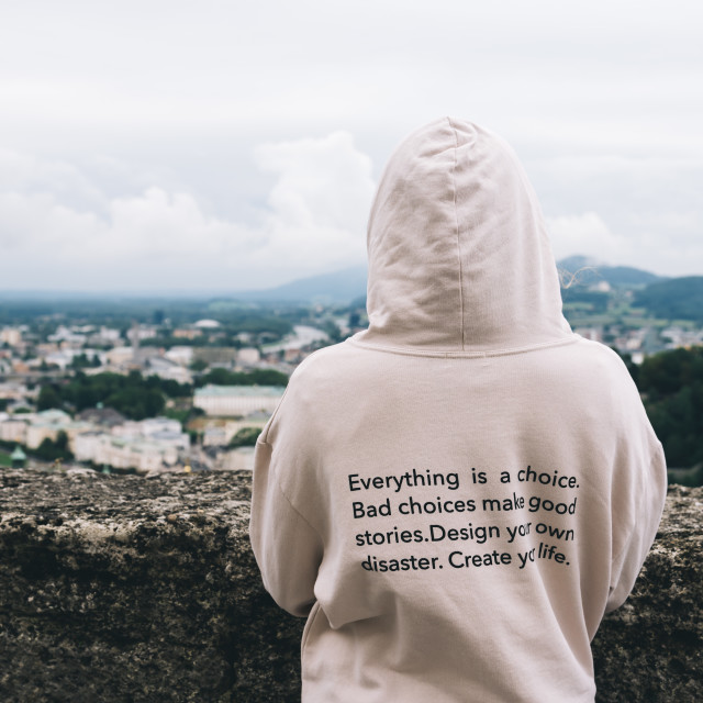 """""""Woman wearing hoodie with inspirational quote against cityscape"""" stock image"""