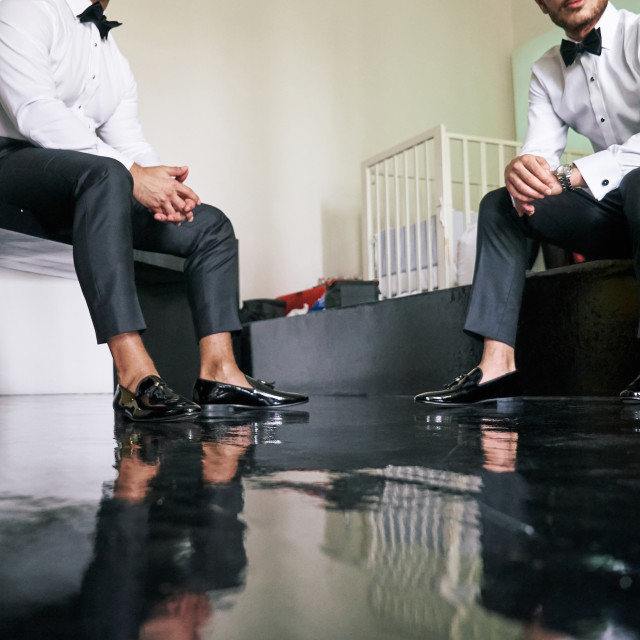 """""""Two man is sitting, relaxing during getting ready, preparation before the wedding ceremony start, black wooden floor - low angle"""" stock image"""