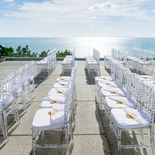 """The ghost chairs setup for modern beach wedding venue with panoramic ocean view"" stock image"