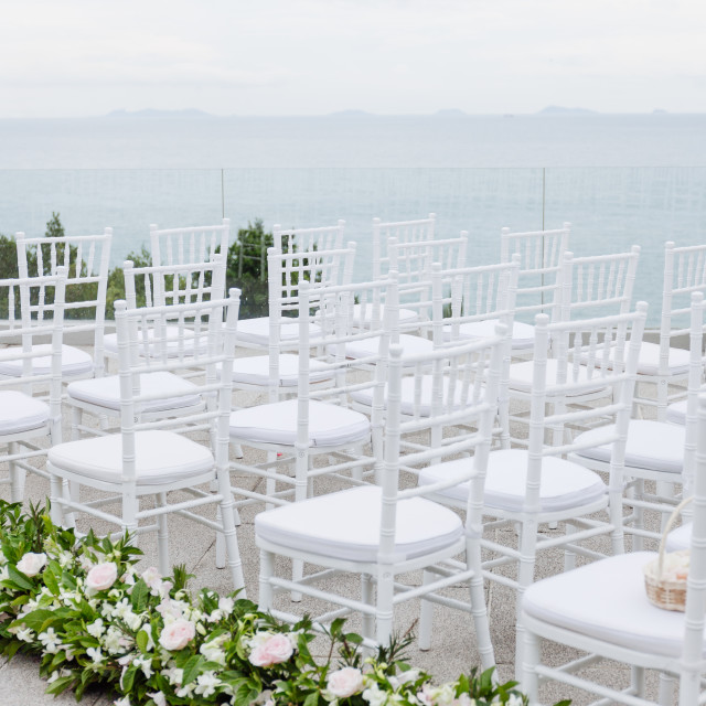 """The white chiavari chairs setup for modern beach wedding venue with flowers decoration on aisle"" stock image"