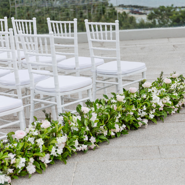 """""""The white chiavari chairs setup for modern beach wedding venue with flowers decoration on aisle"""" stock image"""