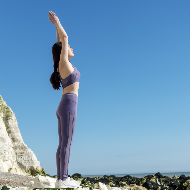 """""""woman practicing yoga on the rocks by the sea with blue sky background"""" stock image"""