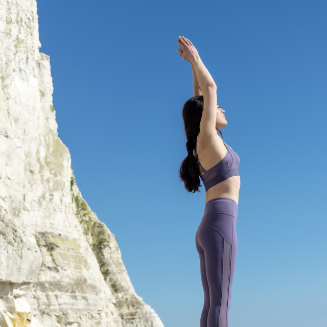"""woman practicing yoga on the rocks by the sea with blue sky background"" stock image"