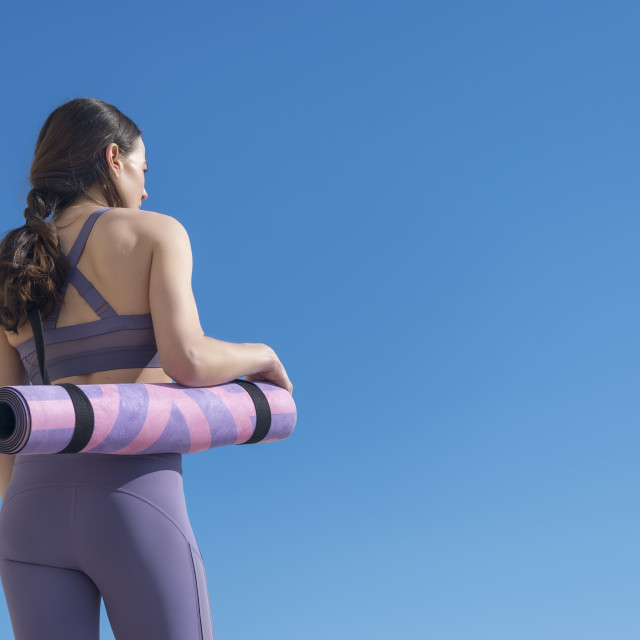 """back view of a woman carrying a rolled up yoga mat with blue sky background"" stock image"