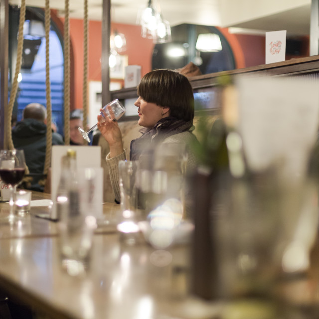 """""""Single, alone, young adult woman drinks wine in pub"""" stock image"""