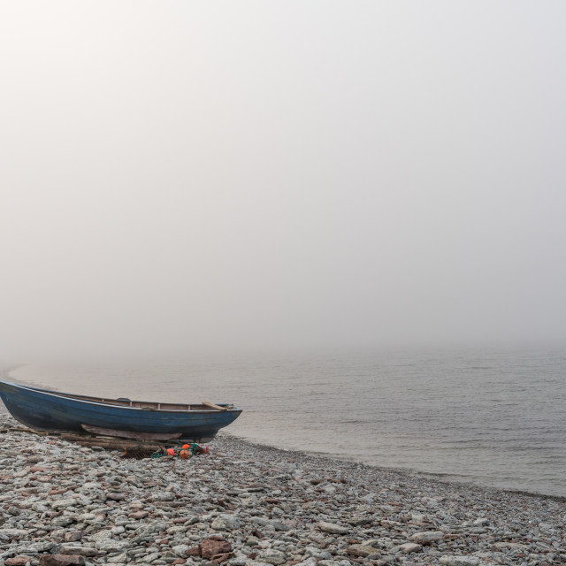 """Lone landed rowboat by seaside"" stock image"