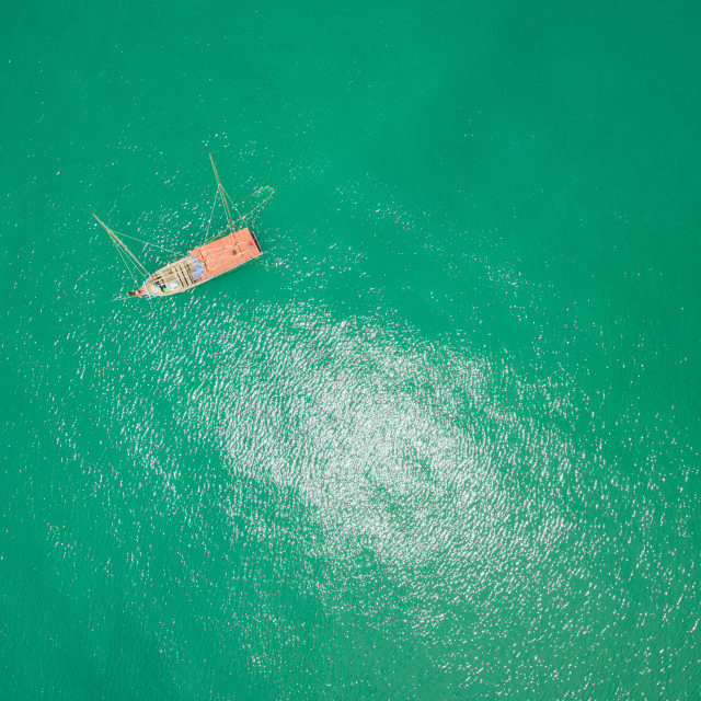 """Aerial view of fishing boat on emerald tropical sea"" stock image"