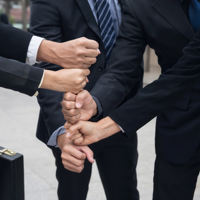 """""""business team stacking hands in city"""" stock image"""