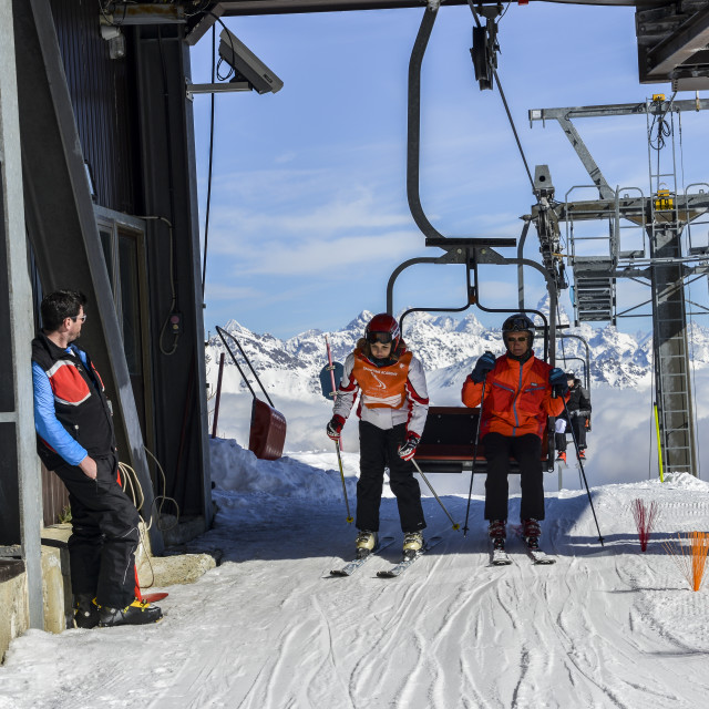 """""""Older man and teenager get off chairlift at ski resort with majestic Italian..."""" stock image"""