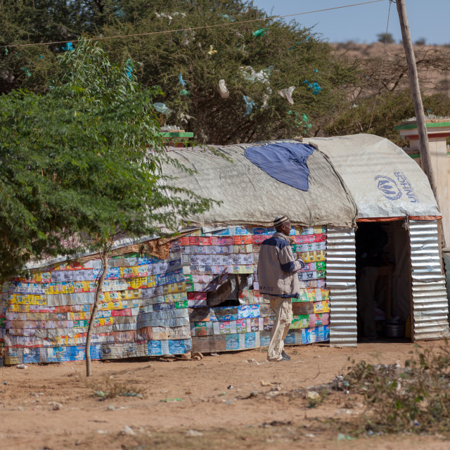 """Somali man in front of a slum hut made of corrugated iron and canvas, Woqooyi..."" stock image"