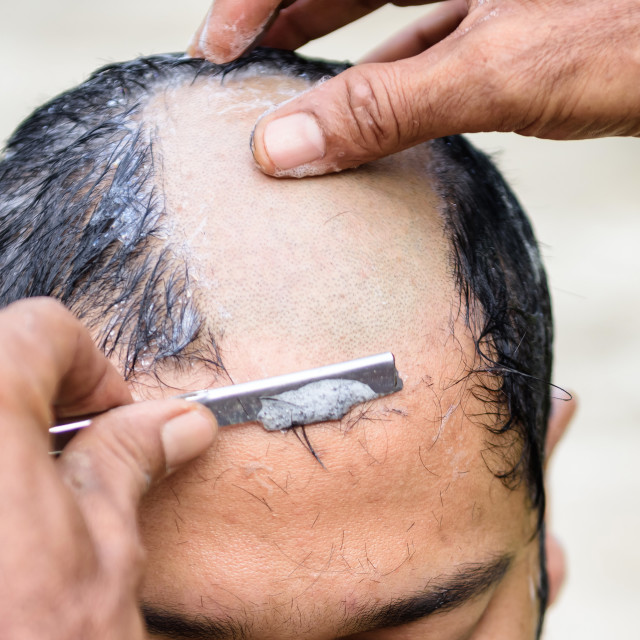 """Shaved hair for ordained Buddhist man"" stock image"
