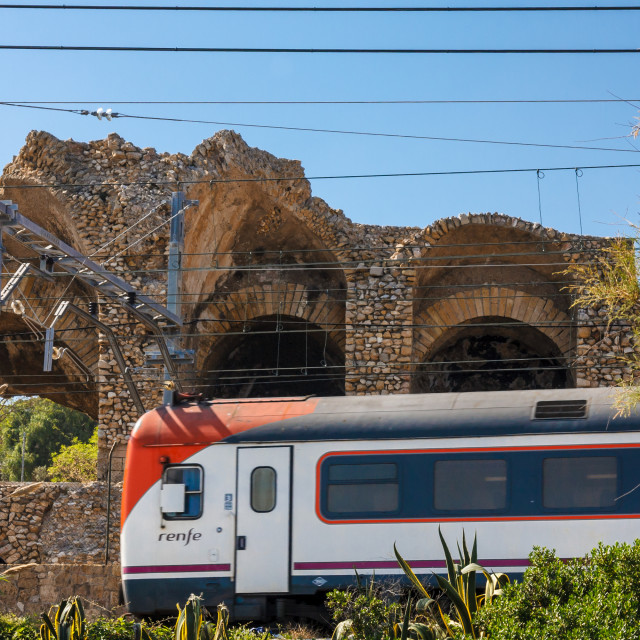 """Local regional 'renfe' train on track passing ancient roman amphitheatre"" stock image"