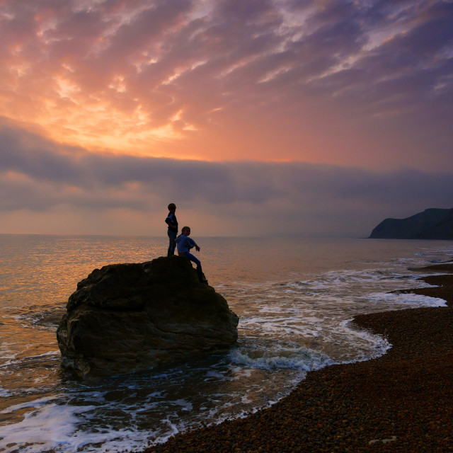 """Children on Rock Dorset Beach Sunset"" stock image"