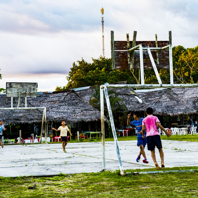 """""""Kids playing football near the Amazon rainforest of Iquitos"""" stock image"""