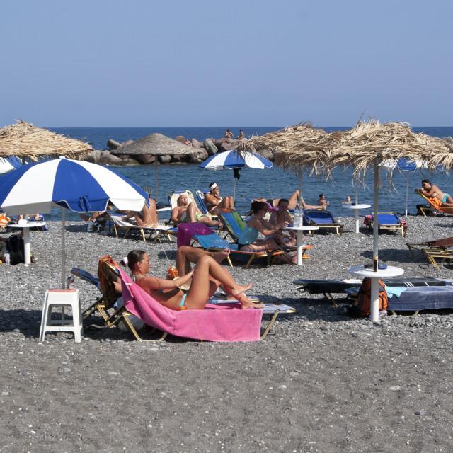 """Sun Worshippers on Santorini Beach"" stock image"