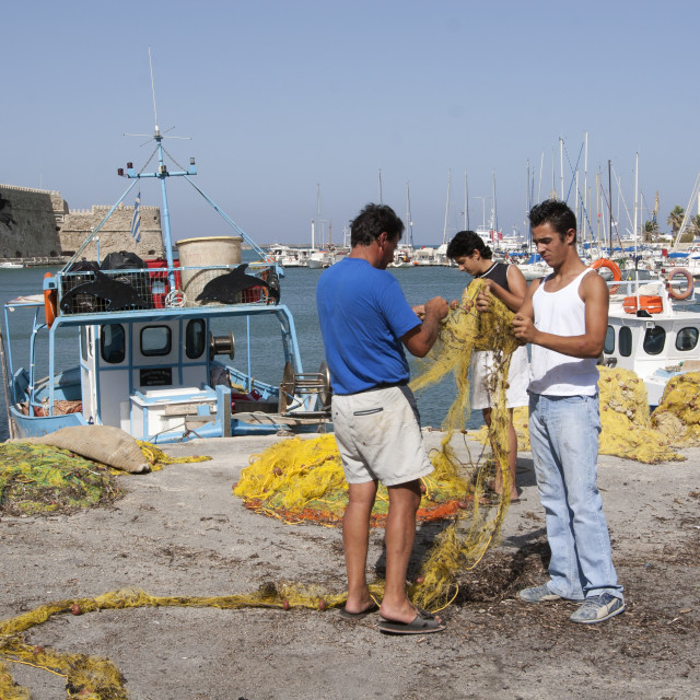 """Fishermen Mending their Nets in Irakleio Harbour"" stock image"