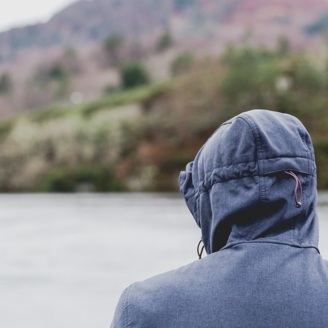 """""""Man with a hood on head stands back to camera"""" stock image"""
