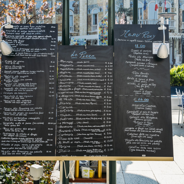 """""""Menu and prices in English and Italian on a billboard on the streets of Lido"""" stock image"""