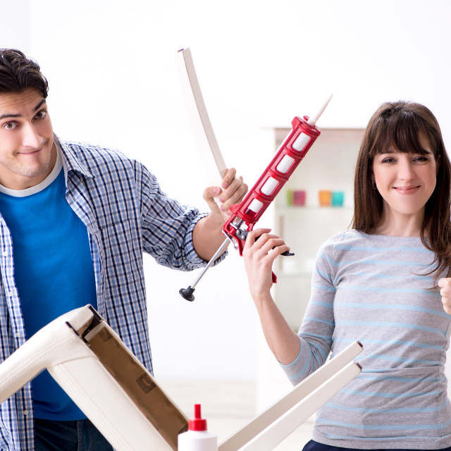 """""""Wife helping husband to repair broken chair at home"""" stock image"""