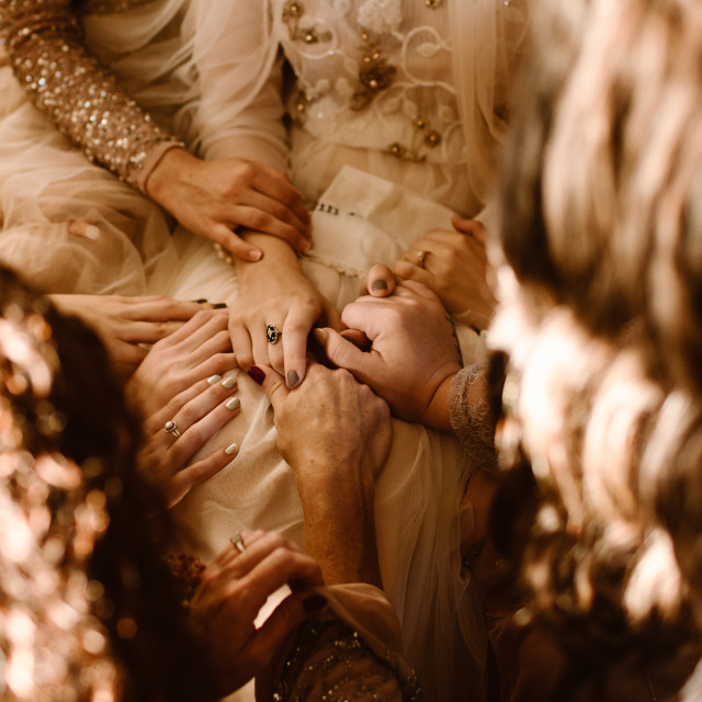"""A Group of Woman Holding Multiple Hands and Praying"" stock image"