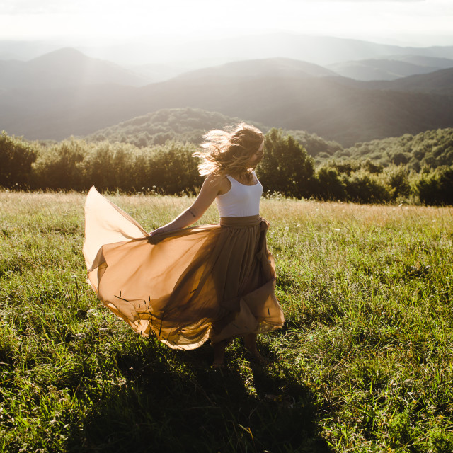 """Woman with long dress running in a meadow in the mountains"" stock image"