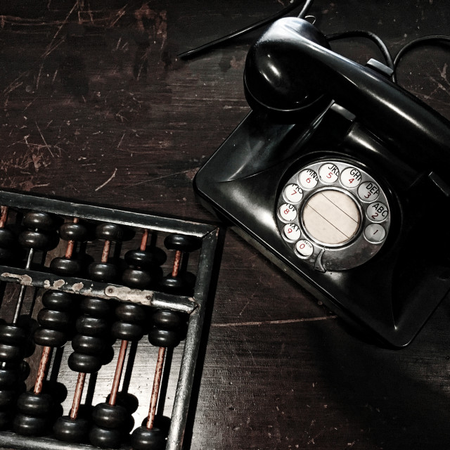 """""""Antique dial telephone and abacus on the wooden table"""" stock image"""