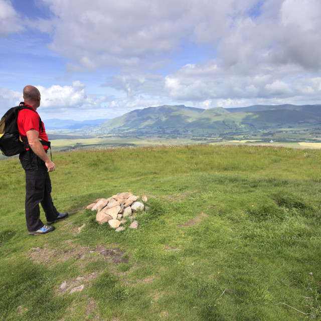 """Walker at the summit of Great Mell Fell, Lake District National Park, Cumbria..."" stock image"