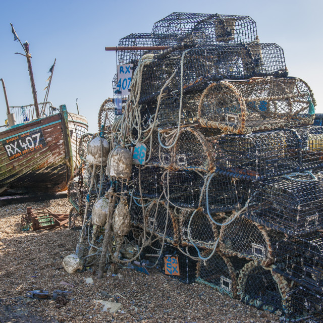 """lobster pots stacked on a beach next to a fishing boat"" stock image"