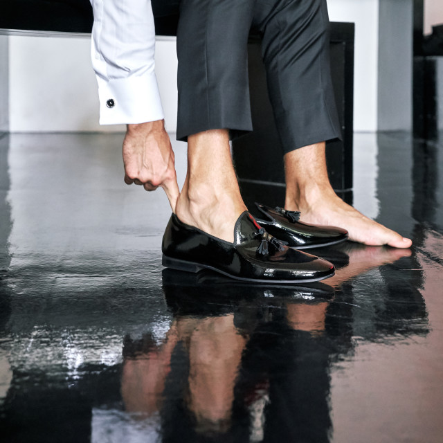 """""""A man is wearing black glossy cut shoes, to prepare for the wedding ceremony, black wooden floor - closed up, low angle"""" stock image"""