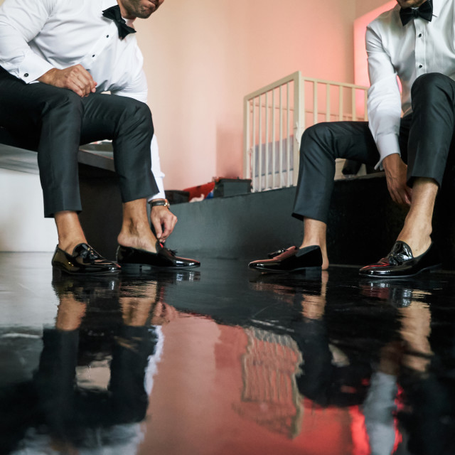 """""""Two man wears slip-on black glossy shoes, to prepare for wedding ceremony, black wooden floor - low angle"""" stock image"""