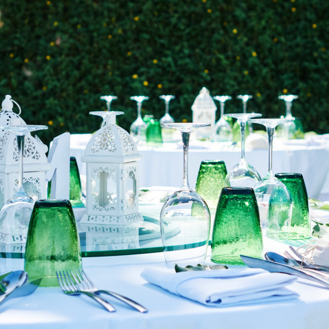 """Reception dinner table preparation, green glass, white and green theme"" stock image"