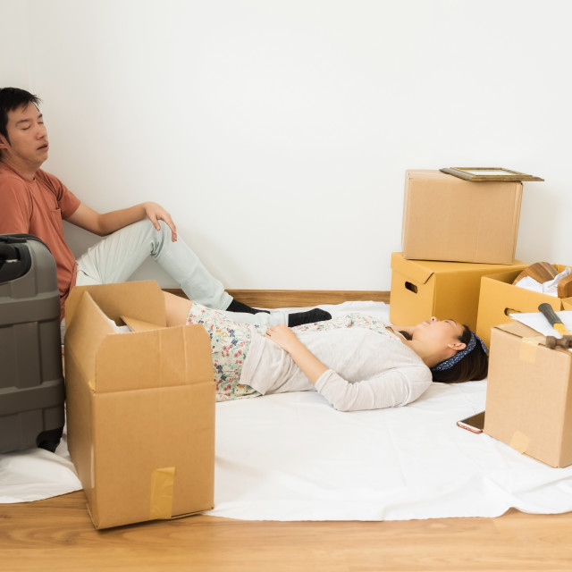 """Tired couple sleep at new moving house"" stock image"
