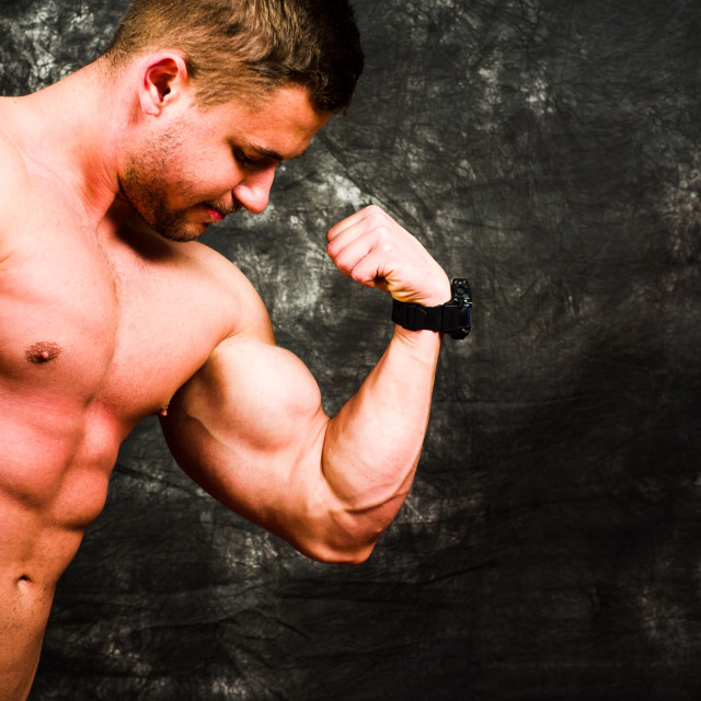 """Bodybuilder flexing muscles against dark background"" stock image"