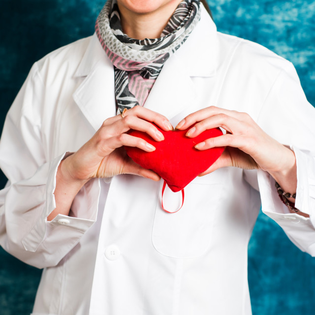 """Female doctor holding a red heart"" stock image"