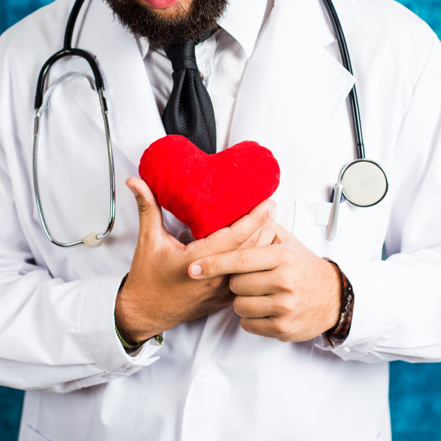 """Doctor holding a red heart toy"" stock image"
