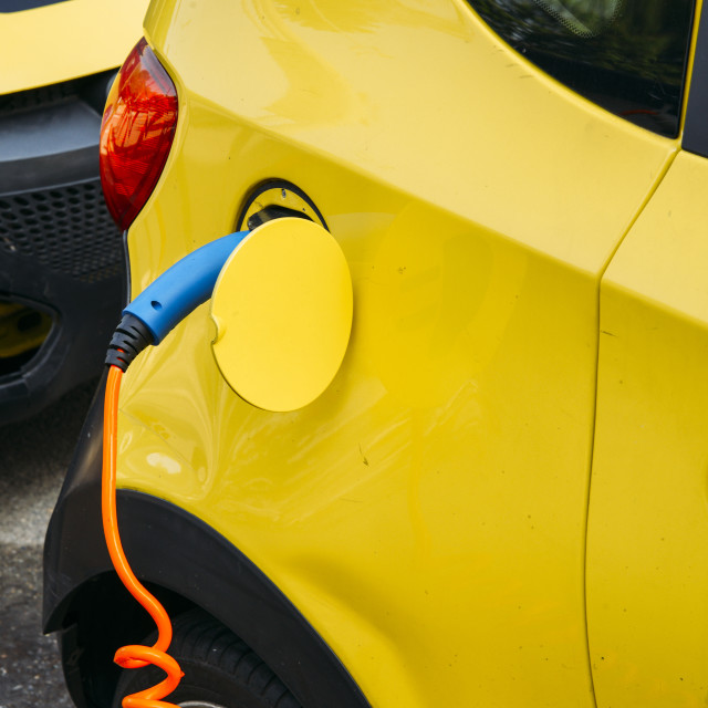 """""""Close up of car being charged electronically at a public rechargeable dock..."""" stock image"""