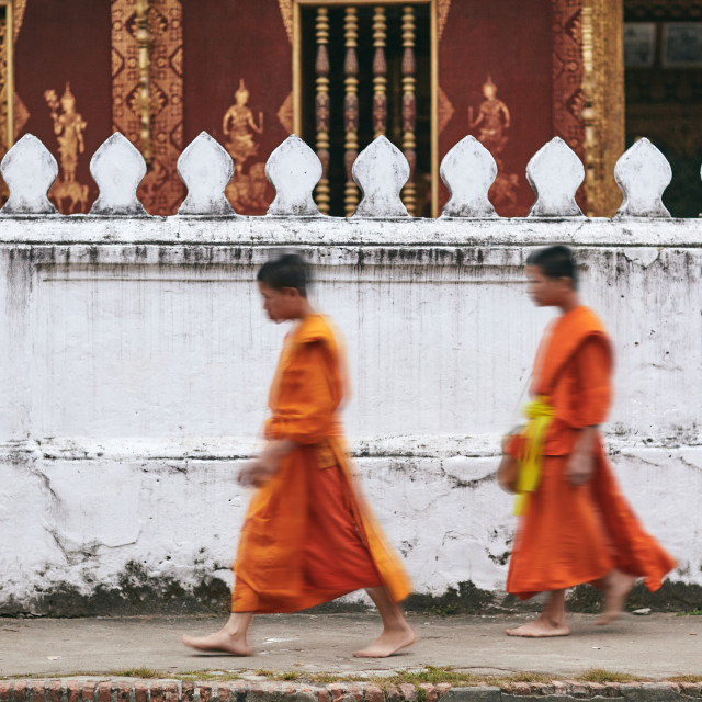"""Luang Phrabang / Laos - June 29, 2010: 2 blurred of young monk walking infront of the temple wall"" stock image"